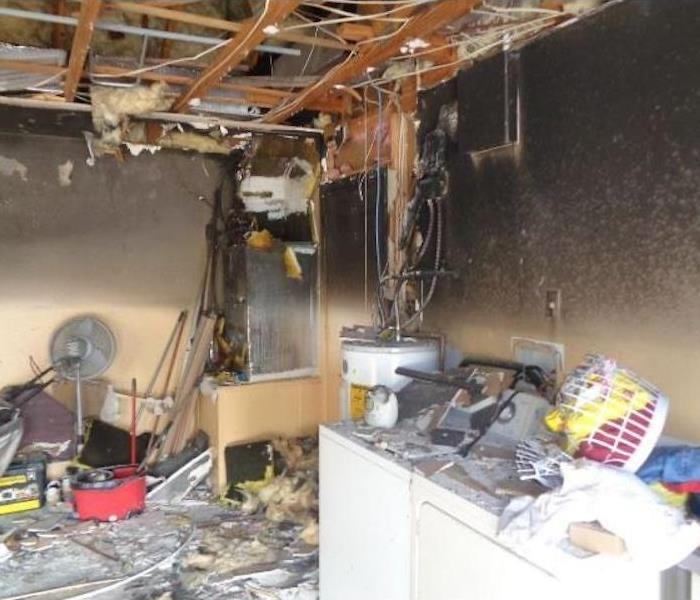 Utility room with extreme fire damage around furnace and appliances