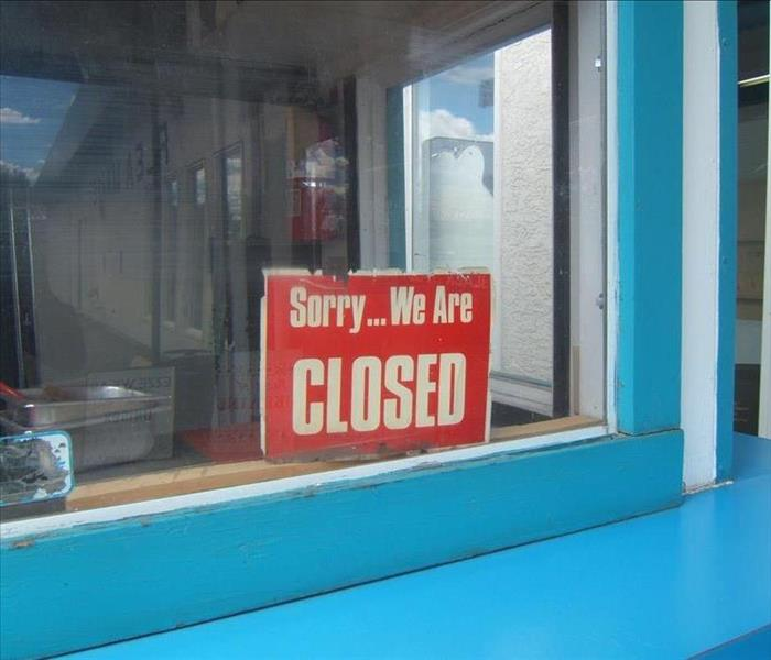 shop window with a sorry were closed sign