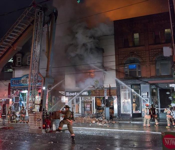 night time 4 store fronts with fire trucks and water hoses